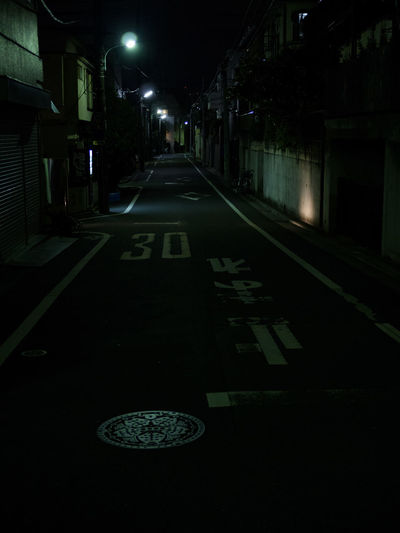 Empty road along illuminated street lights