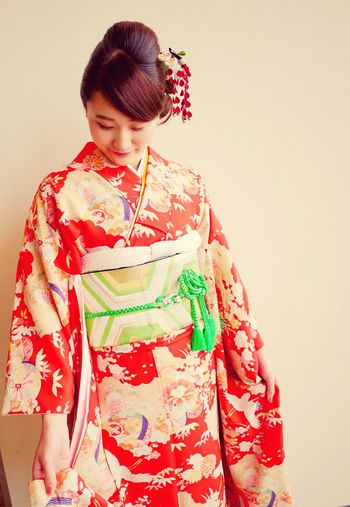 Young Woman Wearing Kimono Against Beige Wall