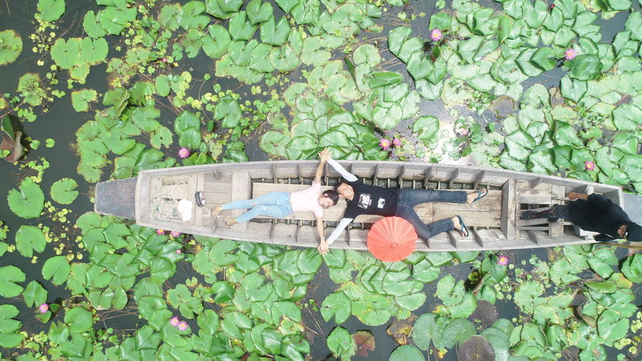 High angle view of couple lying in boat on lake