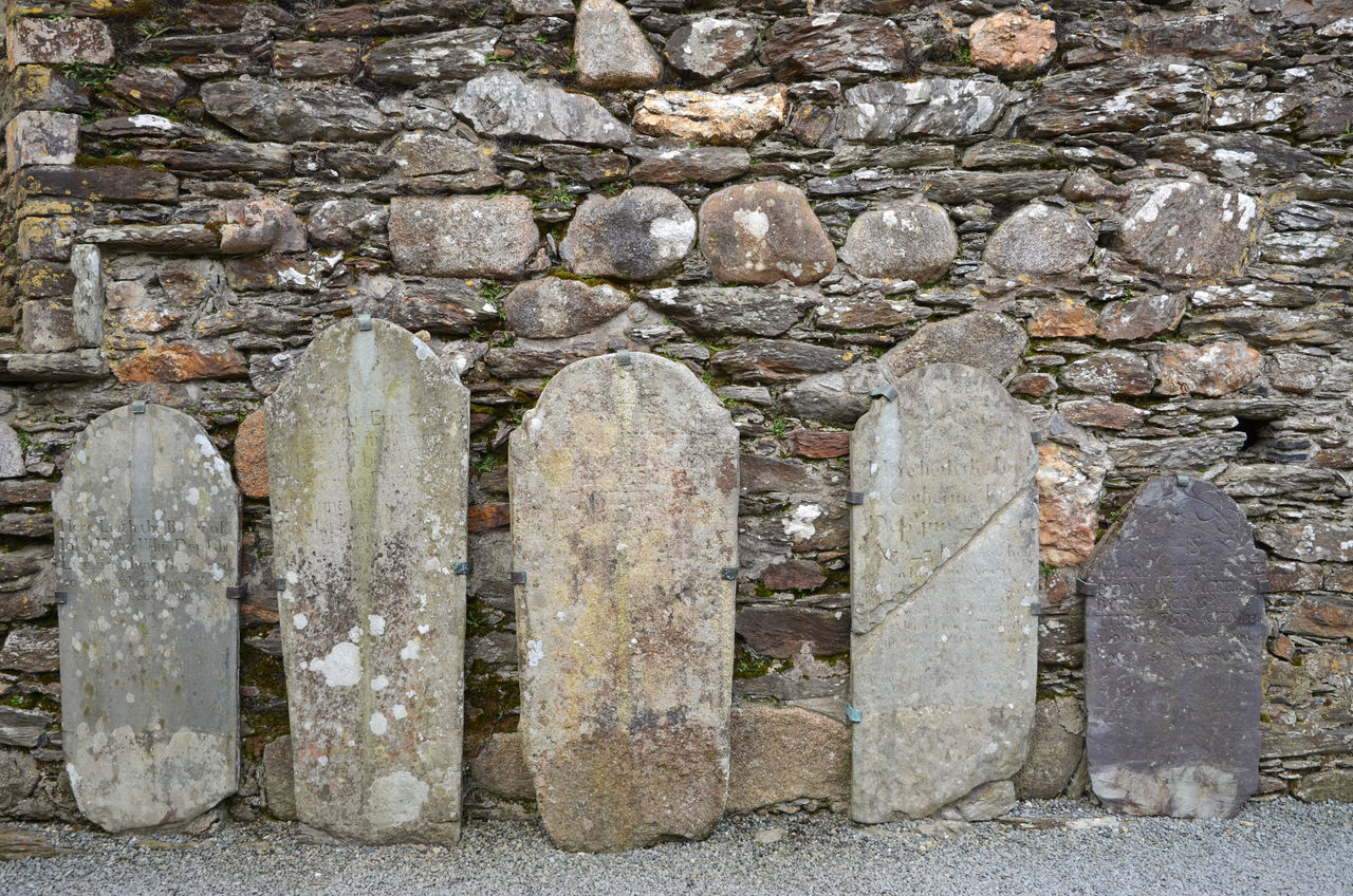 Ancient tombstones leaning against stone wall