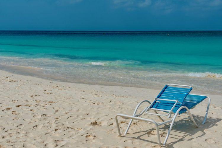 Empty chair at beach against blue sky