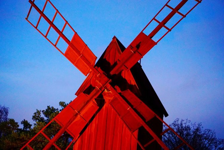 """""""When the wind of change blows, some people build walls and others build windmills"""" - Chinese proverb Red Windmill Closeup Evening Illuminated Red Against Blue - Traveling in Sweden"""