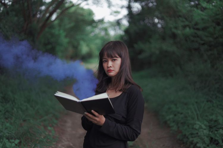 Portrait of woman holding book while standing in forest