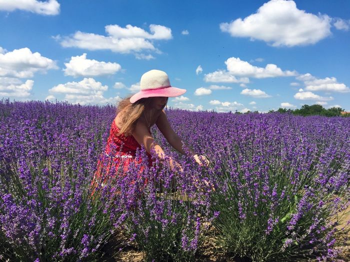 Woman Amidst Lavender Flowers On Field Against Sky