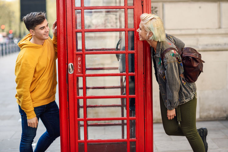 Young happy couple of friends near a classic British red phone booth Two People Real People Women Togetherness Casual Clothing Three Quarter Length Red Lifestyles Young Women Day People Standing Adult Young Adult Architecture Focus On Foreground Blond Hair Bonding Leisure Activity Phone Booth Red London