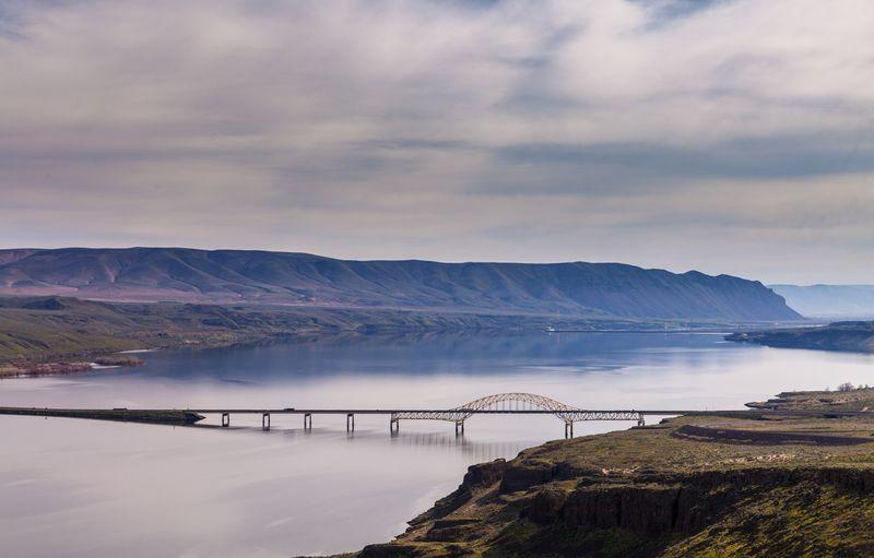 Scenic view of bridge over bay against sky