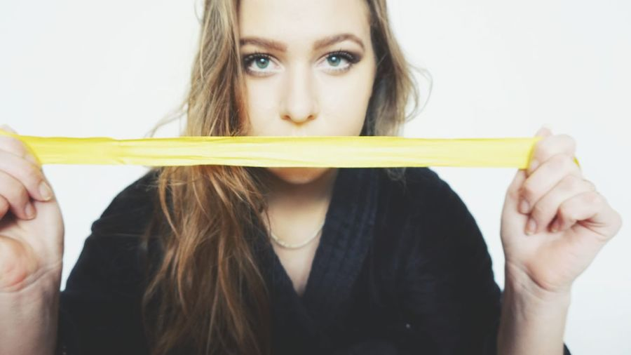 Portrait of young woman stretching yellow strap against white background