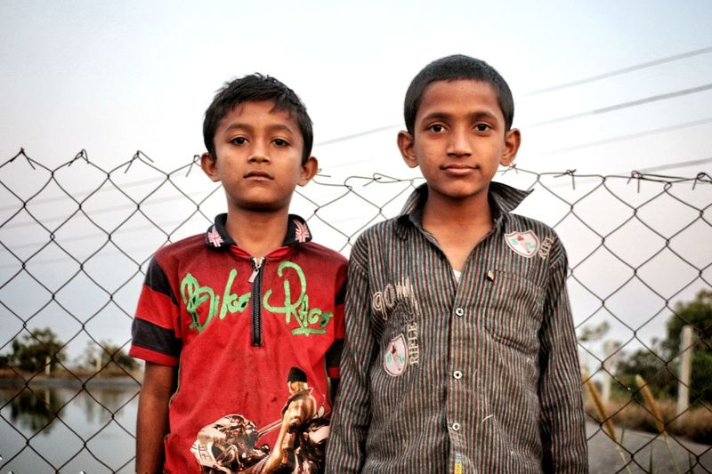 Portrait of boys standing against chainlink fence