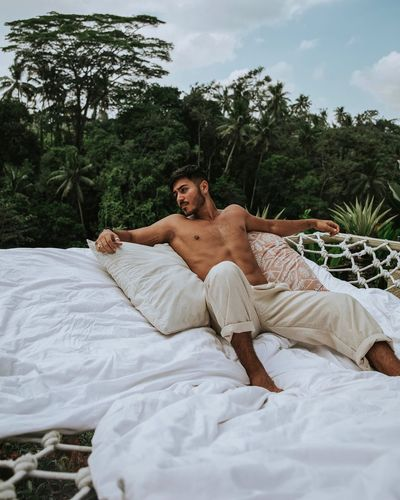 Shirtless young man relaxing on bed against trees in forest