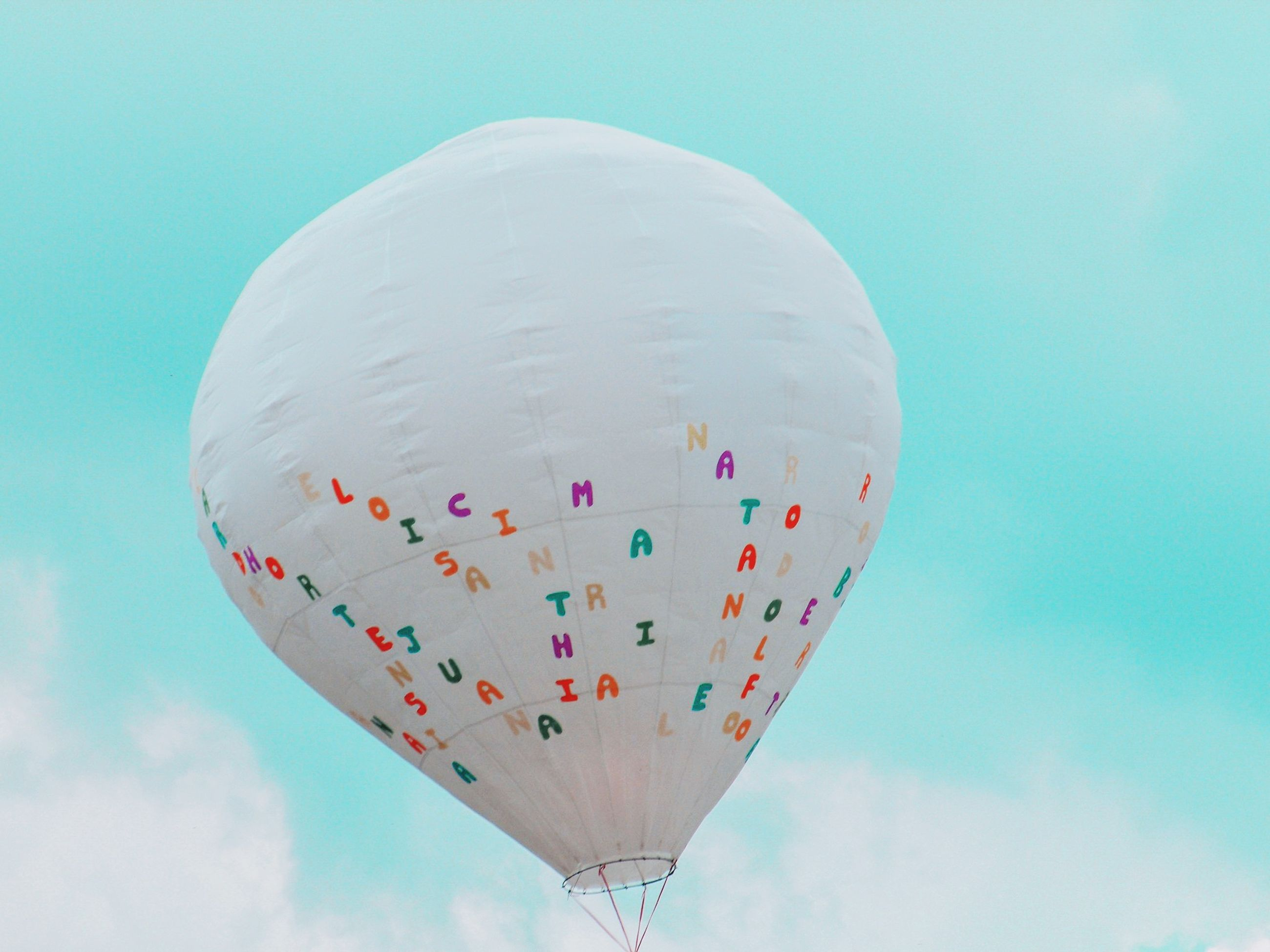 sky, balloon, flying, low angle view, nature, mid-air, day, multi colored, cloud - sky, transportation, hot air balloon, air vehicle, blue, outdoors, no people, adventure, travel, pattern, white color, motion, ballooning festival