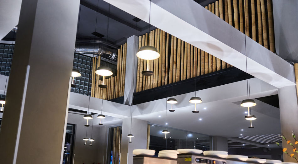 Low angle view of illuminated pendant lights in building