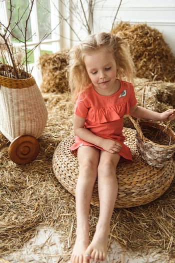 Cute girl sitting on hay