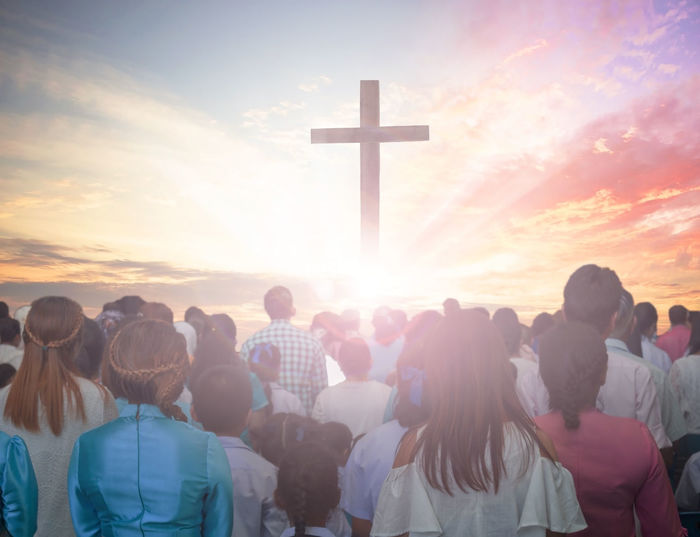 Digital Composite Image Of Crowd And Cross Against Cloudy Sky During Sunset