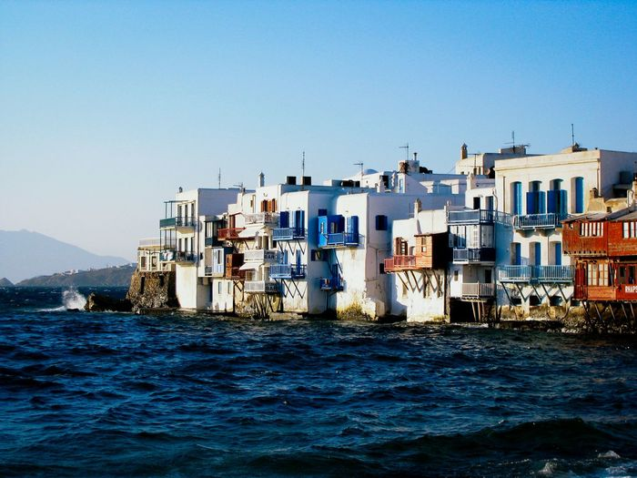 Residential district by sea against clear sky in mykonos