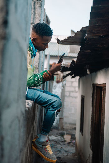 Young man using mobile phone in building