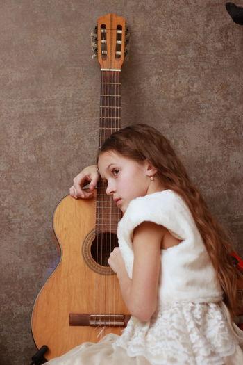 Sad girl sitting by guitar against wall