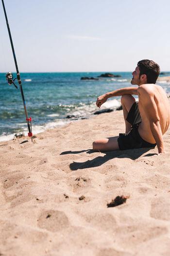 Full length of shirtless man on beach against sky