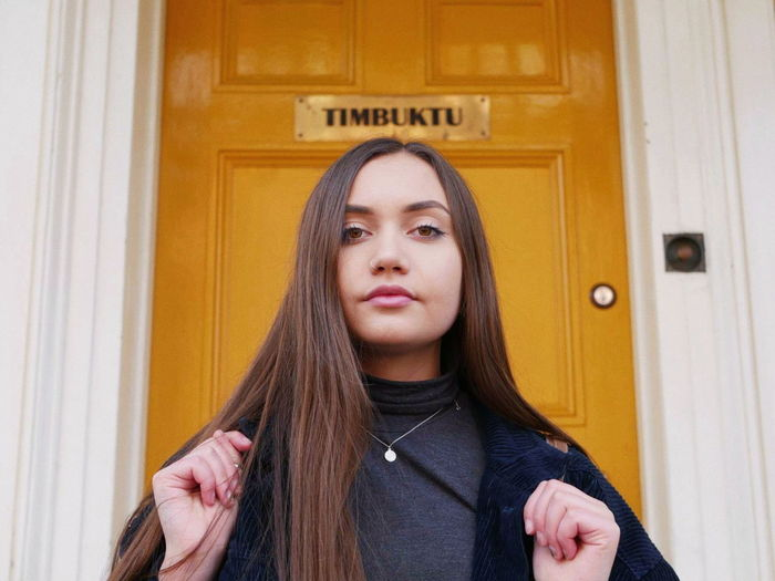 Portrait of young woman standing against door at home