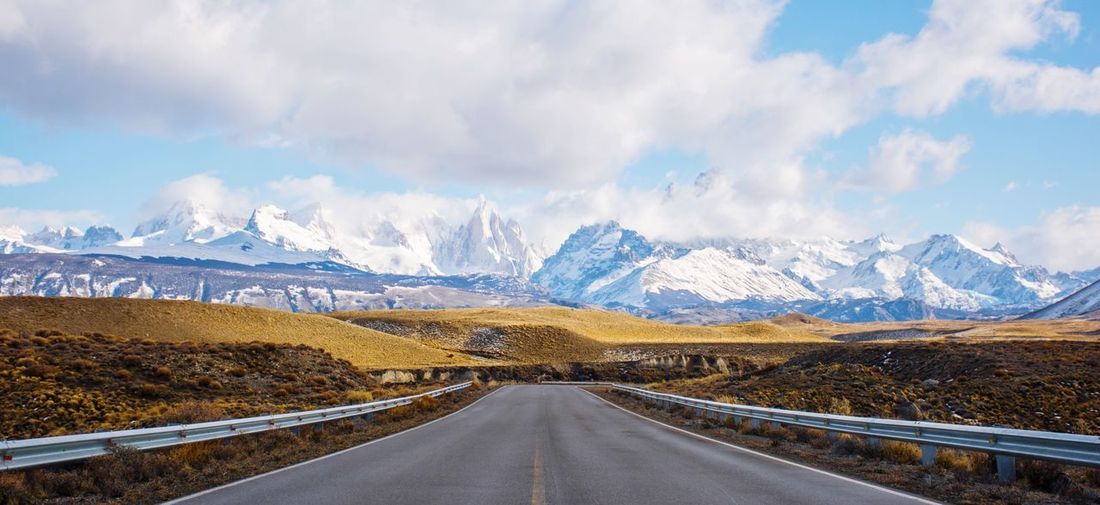 Panoramic view of empty road amidst snowcapped mountains against sky