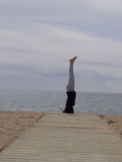 Full length of woman practicing headstand at beach against sky