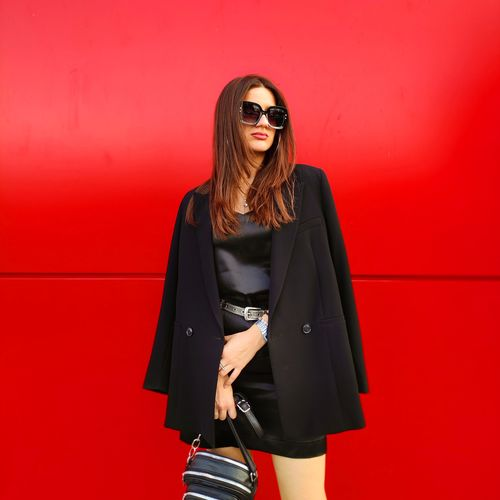 Young woman wearing sunglasses standing against red wall