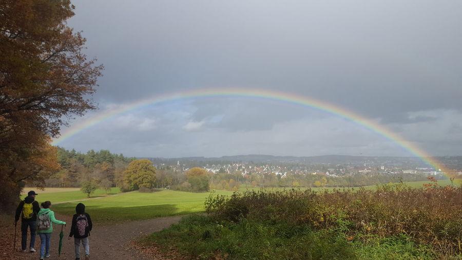 People on field against rainbow in sky
