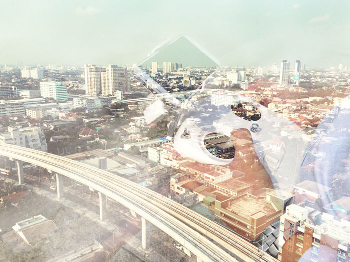 Digital composite image of man using technology against cityscape