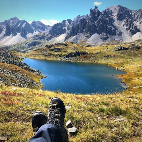 Low section of man relaxing on field by lake by mountains