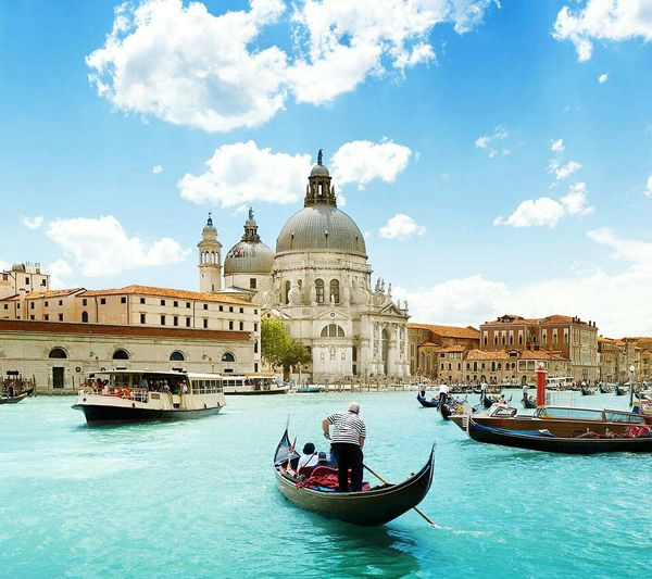 Ferry With Gondolas Sailing In Grand Canal By Santa Maria Della Salute Against Sky