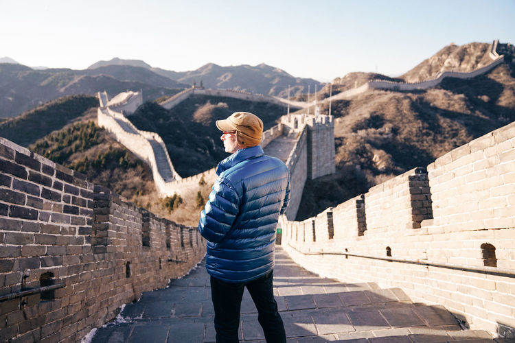 Rear view of man standing on steps at great wall of china
