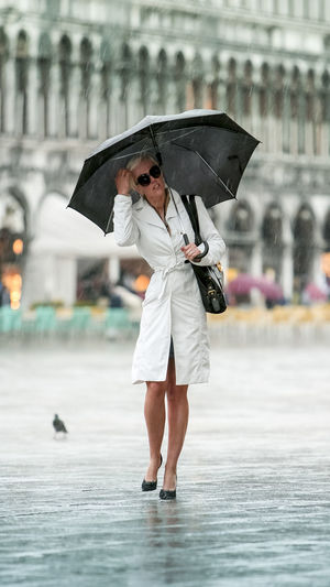 Full length of woman holding umbrella during rainy season
