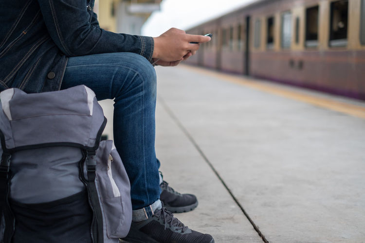 Low section of man with train on railroad station platform