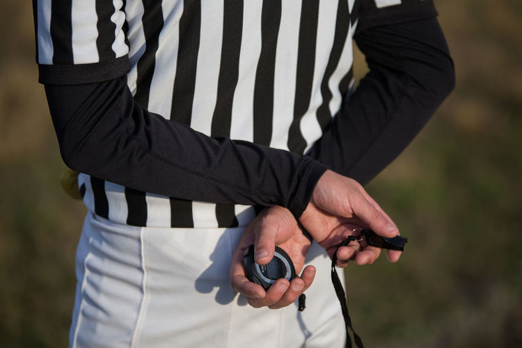 Midsection of referee holding whistle and stopwatch