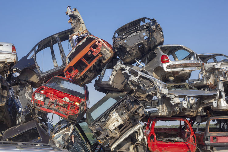 Low Angle View Of Abandoned Cars In Junkyard Against Sky