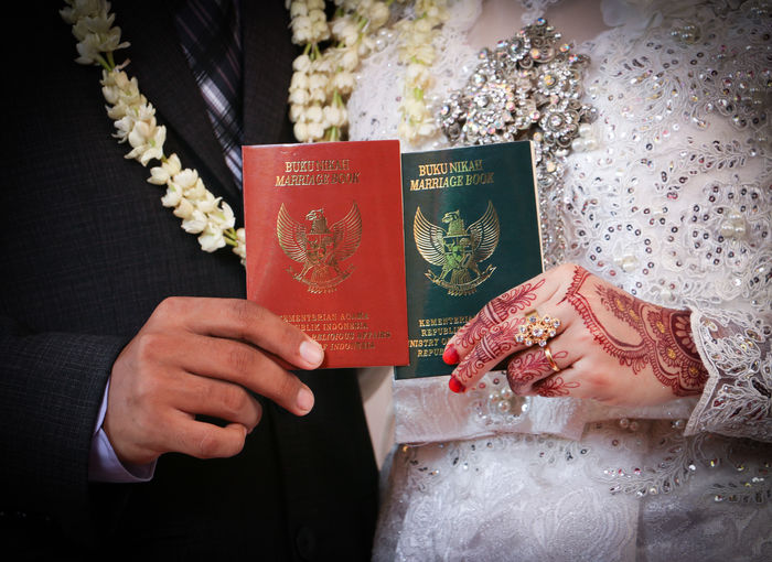 Midsection of bride and bridegroom holding passports
