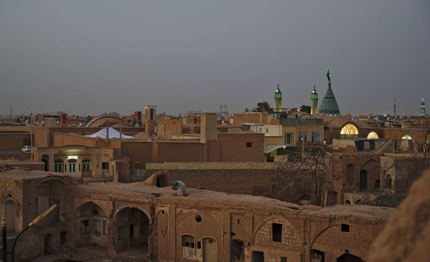Traditional buildings and mosque with minarets in city in desert against clear sky at sunset
