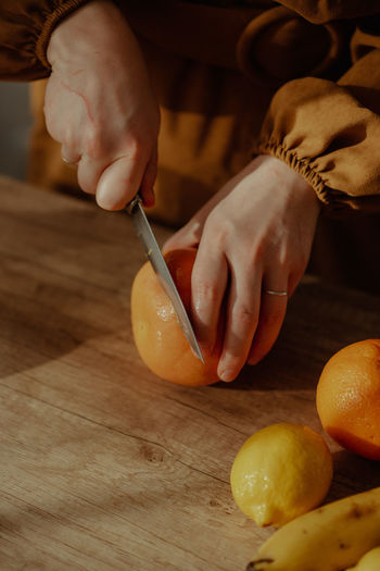 Midsection of person preparing fruits on cutting board