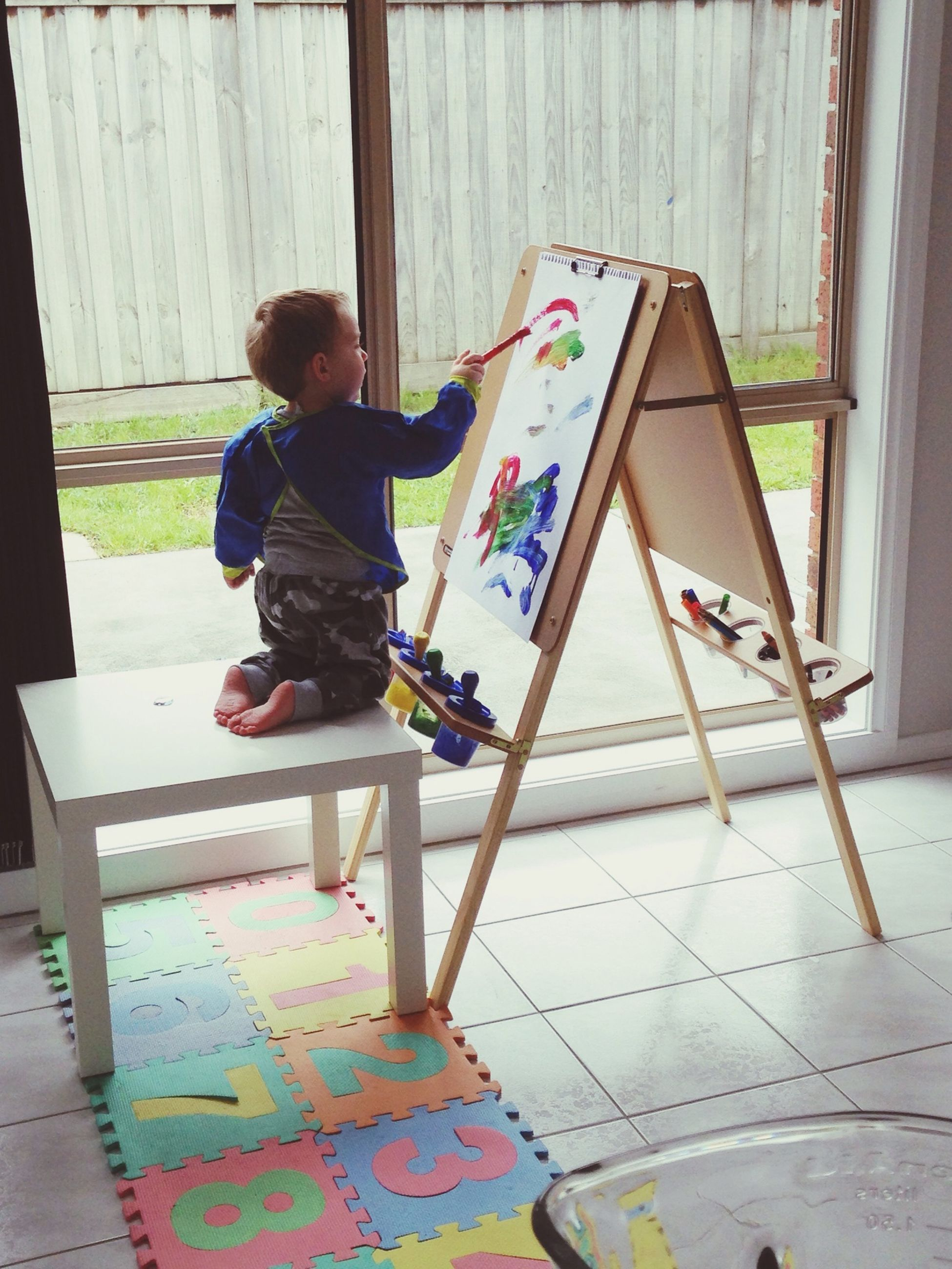 full length, lifestyles, leisure activity, casual clothing, childhood, sitting, chair, built structure, indoors, architecture, relaxation, boys, elementary age, day, wood - material, table, sunlight, person