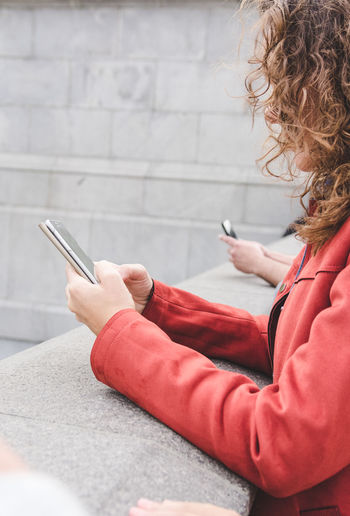 Side view of mature woman using smart phone while standing by retaining wall