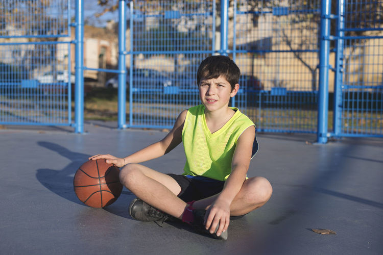 Young basketball player sitting on the court wearing a yellow sleeveless Sunlight Adult Athlete Ball Basketball - Sport Basketball Player Court Day Exercising Full Length Healthy Lifestyle Indoors  Leisure Activity Lifestyles One Person People Playing Real People Sitting Sport Sports Clothing Sports Team Sports Uniform Teenager Young Adult