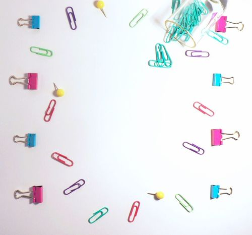 White desk scene overhead lay flat office supplies Paper Clip Multi Colored No People Typography Friendly Binder Clips Push Pins Blogger Teacher Overhead View Desk Close-up White Background Arrangement Large Group Of Objects Studio Shot Crafts DIY EyeEmNewHere Above View