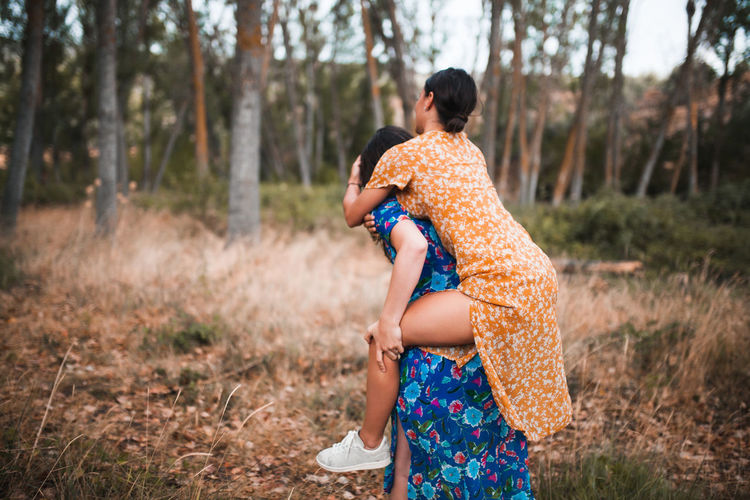 Woman piggybacking girlfriend in forest