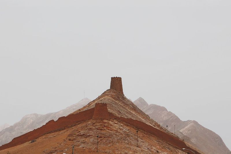 Low angle view of castle on mountain against sky