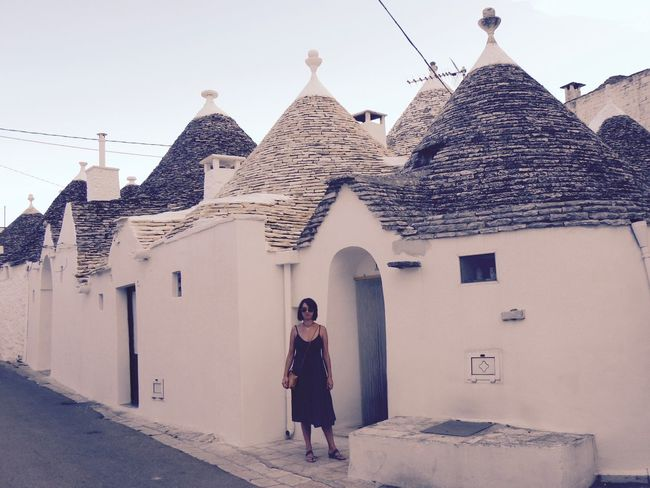 Alberobello Alberobello - Puglia Alberobello City Alberobellocity Alberobelloexperience Alberobellophotocontest Architecture Building Exterior Built Structure Day Front View Full Length House Lifestyles Looking At Camera One Person Outdoors People Portrait Real People Standing Young Adult Young Women Let's Go. Together. Your Ticket To Europe
