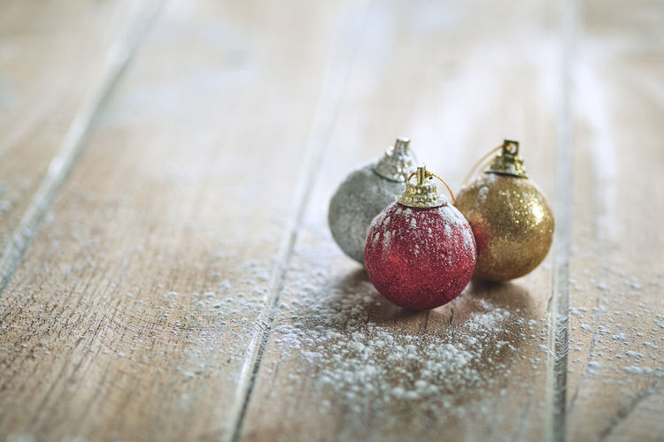 Close-Up Of Christmas Ornaments With Flour On Table