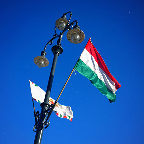Low angle view of hungarian flag on street light against sky