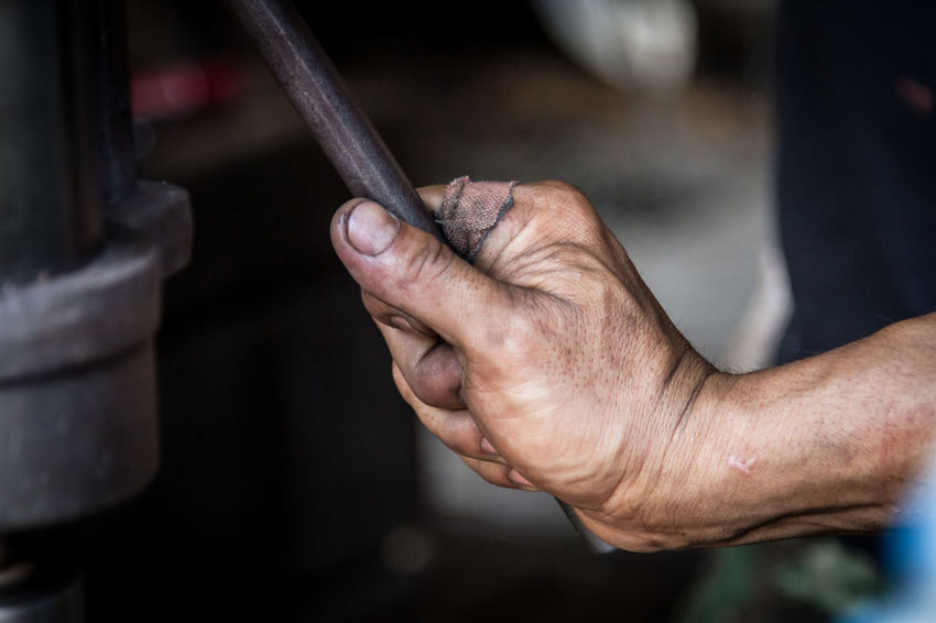 Adult Close-up Effort Gripping Hand Holding Human Body Part Human Hand Human Limb Indoors  Mechanic Men Occupation One Person Repairing Senior Adult Skill  Strength Work Tool Working