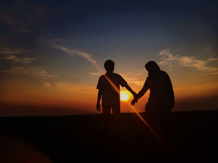 Silhouette friends against sky during sunset