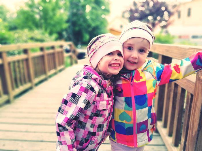 Portrait of smiling girls standing on footbridge