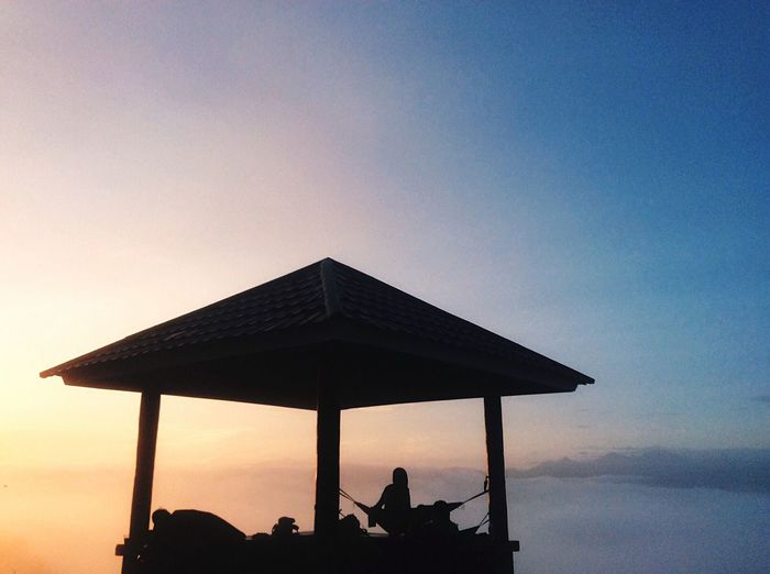 Silhouette woman in gazebo against sky during sunrise